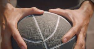 Retrato do close up das mãos masculinas afro-americanos desportivas que guardam uma bola do basquetebol na corte na cidade urbana filme