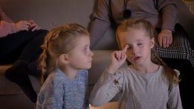 Retrato do close-up das meninas caucasianos pequenas que olham o filme atentamente e que falam um com o otro na casa confortável filme