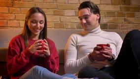Retrato do close-up de dois amigos caucasianos novos perto do chá bebendo do sofá e da fala um com o otro na casa confortável video estoque