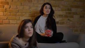Retrato do close up de dois amigos fêmeas novos que olham a tevê ao descansar em um apartamento acolhedor dentro imagens de stock royalty free