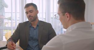 Retrato do close up de dois homens de negócios atrativos que têm uma discussão formal no escritório dentro filme