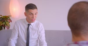 Retrato do close up de dois homens de negócios caucasianos que têm uma discussão de encontro dentro no escritório Homem novo que  filme