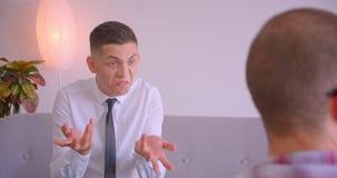 Retrato do close up de dois homens de negócios caucasianos que têm uma discussão de encontro dentro no escritório Homem novo que  video estoque