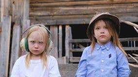 Retrato do close-up de duas crianças bonitas das meninas que levantam no capacete empoeirado vídeos de arquivo
