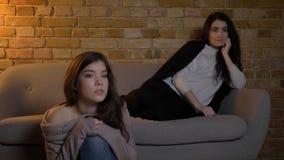 Retrato do close up de duas meninas bonitas novas que olham a tevê com expressão facial curiosa ao descansar em um apartamento ac fotos de stock