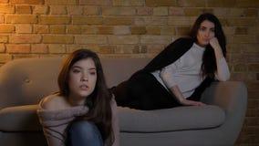 Retrato do close up de duas meninas bonitas novas que olham a tevê com expressão facial fascinada ao descansar em um acolhedor imagem de stock