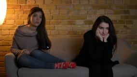 Retrato do close up de duas meninas bonitas novas que olham a tevê junto com a expressão facial entusiasmado ao descansar no fotografia de stock