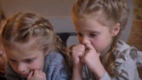 Retrato do close-up de duas meninas caucasianos pequenas que encontram-se no assoalho e que olham na tabuleta atentamente na casa vídeos de arquivo