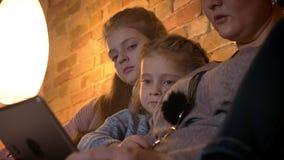 Retrato do close-up de duas meninas caucasianos pequenas que olham na tabuleta atentamente na atmosfera de casa confortável filme