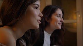 Retrato do close up de duas mulheres bonitas novas que olham a tevê rir felizmente em um apartamento acolhedor dentro fotografia de stock royalty free