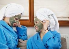 Retrato do close-up de duas mulheres de vista bonitas com uma máscara facial da argila imagens de stock royalty free