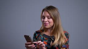 Retrato do close up de imagens de vista da mulher caucasiano nova bonita no telefone com sorriso positivo vídeos de arquivo