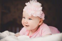 Retrato do close-up de 3 meses bonitos do bebê de sorriso idoso no rosa que encontra-se para baixo em uma cama branca em casa Olh Fotos de Stock