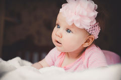 Retrato do close-up de 3 meses bonitos do bebê surpreendente idoso no rosa que encontra-se para baixo em uma cama branca em casa  Fotografia de Stock Royalty Free