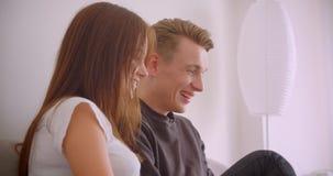Retrato do close up de pares caucasianos bonitos novos usando o portátil que olha um filme junto rir o assento no sofá filme