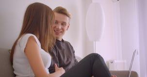 Retrato do close up de pares caucasianos bonitos novos usando o portátil que olha um filme junto rir felizmente o assento sobre vídeos de arquivo