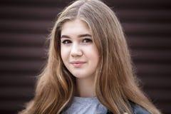 Retrato do close-up de pouca menina à moda bonita da criança com cabelo por muito tempo de fluxo contra uma parede listrada marro foto de stock