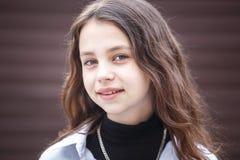 Retrato do close-up de pouca menina à moda bonita da criança com cabelo por muito tempo de fluxo contra uma parede listrada marro foto de stock royalty free