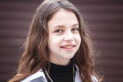 Retrato do close-up de pouca menina à moda bonita da criança com cabelo por muito tempo de fluxo contra uma parede listrada marro imagem de stock royalty free