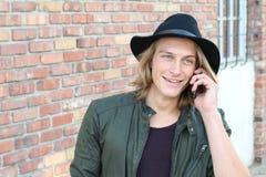 Retrato do close up de rir o homem novo que fala no telefone celular fora imagens de stock royalty free
