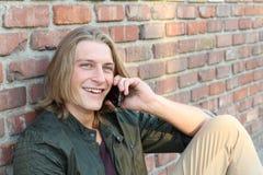 Retrato do close up de rir o homem novo que fala no telefone celular fora imagem de stock