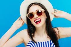 Retrato do close up de rir o modelo fêmea em óculos de sol da forma e em chapéu do verão no fundo azul fotos de stock royalty free