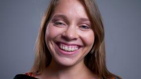 Retrato do close up de rir de sorriso da cara fêmea caucasiano nova feliz e de olhar a câmera filme