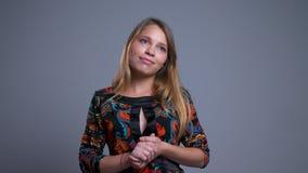 Retrato do close up de sonhar a fêmea caucasiano nova que guarda seus braços thoughfully na frente da câmera video estoque