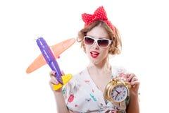 Retrato do close up de ter o divertimento que joga com avião & que mostra a despertador a menina loura bonita do pinup da jovem m Fotografia de Stock Royalty Free