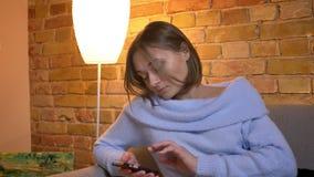 Retrato do close up de texting fêmea caucasiano bonito novo no telefone e de fixar seu cabelo ao sentar-se no sofá em acolhedor filme