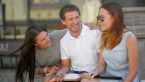 Retrato do close up de três estudantes novos de sorriso ativos que sentam-se no Brench no parque da cidade e que preparam-se para vídeos de arquivo