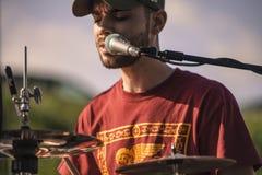 Retrato do close-up de um baterista que canta no microfone imagem de stock