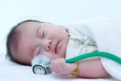 Retrato do close up de um bebê de sono bonito com estetoscópio Fotografia de Stock Royalty Free