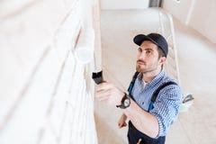 Retrato do close-up de um decorador que usa o rolo durante o trabalho Imagem de Stock