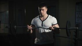 Retrato do close up de um exercício muscular do homem com o barbell no gym vídeos de arquivo