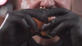 Retrato do close-up de um homem farpado em luvas pretas que come um hamburguer saboroso O homem que aprecia o fast food de dar ág vídeos de arquivo