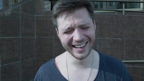 Retrato do close-up de um homem novo de riso Contra o contexto de uma construção moderna das telhas Uma pessoa de sorriso aponta  vídeos de arquivo