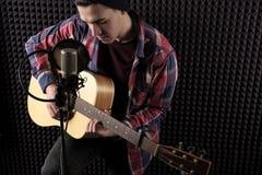 Retrato do close up de um indivíduo novo em uma camisa de manta que joga uma guitarra na frente de um microfone contra uma parede foto de stock