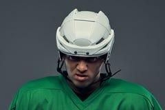 Retrato do close-up de um jogador de hóquei profissional irritado em um sportswear protetor e do capacete em um fundo cinzento fotos de stock