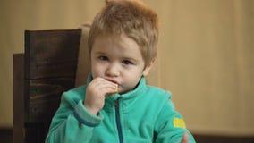 Retrato do close-up de um menino que coma uma pizza e mantenha os polegares Pizza saboroso Menino caucasiano pequeno bonito que c vídeos de arquivo