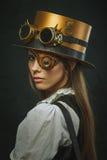 Retrato do close-up de um steampunk, de um chapéu e de um eyecup bonitos da menina imagem de stock