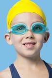 Retrato do close-up de um tampão vestindo e de óculos de proteção da nadada da moça feliz sobre o fundo azul Fotografia de Stock Royalty Free