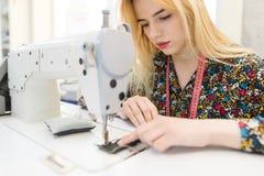 Retrato do close up de uma costureira nova bonito que senta-se e que costura em uma máquina de costura fotografia de stock royalty free