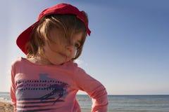 Retrato do close-up de uma jovem criança bonito, sorrindo na praia em um tampão vermelho Imagens de Stock Royalty Free