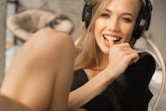 Retrato do close up de uma jovem mulher que escuta a música nos fones de ouvido Fotografia de Stock