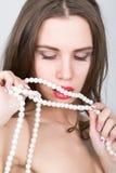 Retrato do close-up de uma menina bonita com bordos vermelhos, guardando uma colar da pérola a boca aberta, peroliza toques seus  Fotos de Stock Royalty Free