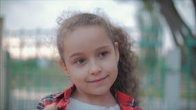 Retrato do close-up de uma menina caucasiano feliz bonito que faz uma cara surpreendida e que sorri então olhando a câmera video estoque
