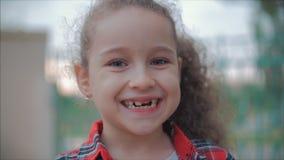Retrato do close-up de uma menina caucasiano feliz bonito que faz uma cara surpreendida e que sorri então olhando a câmera filme