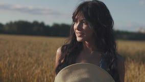 Retrato do close-up de uma menina em um chapéu de palha em um campo de trigo vídeos de arquivo