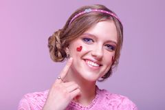 Retrato do close-up de uma menina positiva nova com composição diária profissional em máscaras cor-de-rosa com uma borda e em cor fotos de stock